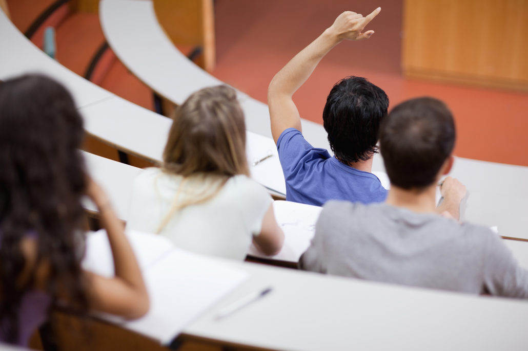 Young student raising his hand while his classmates are taking notes
